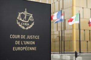 Sign 'cour de justice de l'union europeenne' outside building with flags
